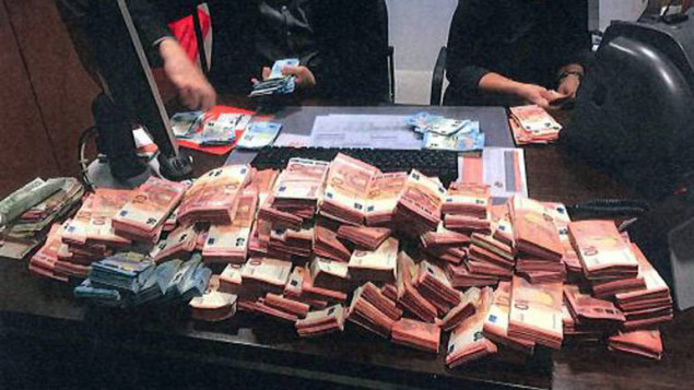 In this image provided by the Belgian Federal Prosecutors Office in Brussels on Tuesday, Nov. 29, 2016, stacks of euros are counted. Belgian authorities say they have helped to break up a major international drug and money laundering ring, detaining seven people and seizing millions of euros, vehicles and firearms. (Xavier Dellicour/Belgian Prosecutors Office via AP)