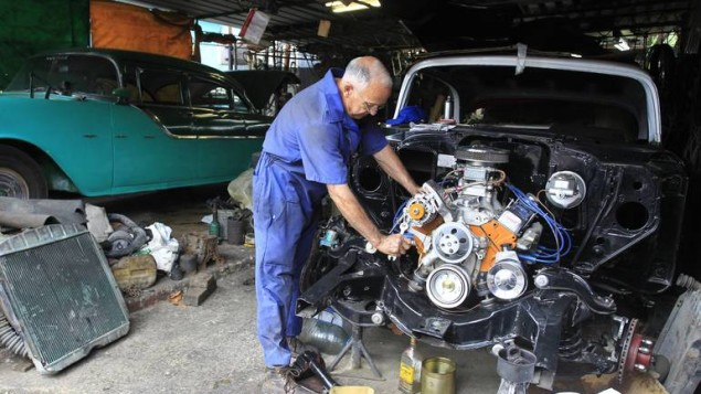 Santiago Rodriguez, 63, car mechanic, repairs a 1957 Chevrolet car in his mechanical workshop in Havana December 25, 2014. Around 60,000 vintage cars have run on Cuba's roads since before the 1959 revolution led by Fidel Castro, but finding a collectible of value is a challenge. For every hidden gem, there are thousands of beaten up clunkers, largely stripped of their original parts. Picture taken December 25, 2014. To match Feature CUBA-USA/AUTOS        REUTERS/Stringer (CUBA - Tags: SOCIETY TRANSPORT BUSINESS)