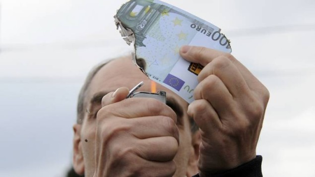 A protester burns a fake one hundred Euro banknote during a demonstration against a new package of tax hikes and reforms in Athens, Greece, May 22, 2016.     REUTERS/Michalis Karagiannis