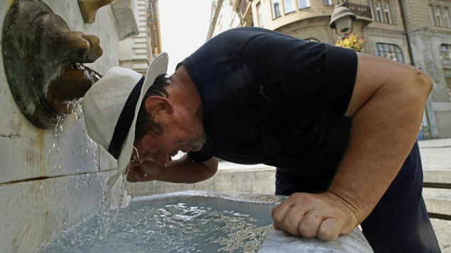 epa04883394 A man holds his head under a water fountain in Belgrade, Serbia, 14 August 2015. Meteorologists were predicting temperatures of up to 39 degrees Celsius in Serbia.  EPA/KOCA SULEJMANOVIC
