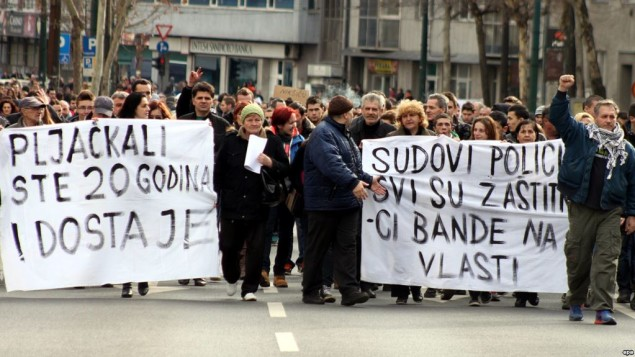 epa04066881 Protesters hold banners reading 'You are robbed of twenty years' and 'The courts and the police are the protectors of the gang in power' and shout slogans during a protest in Sarajevo, Bosnia and Herzegovina, 10 February 2014. Three days after violent protests broke out in the Bosnian capital, people took to the streets again, asking the government to resign.  EPA/ALMIR PANJETA