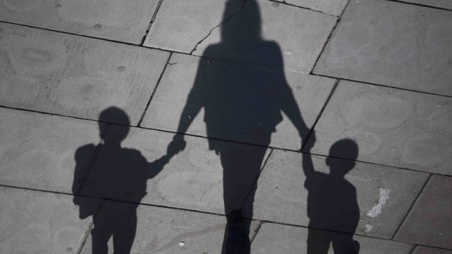 A woman and children cast their shadows as they stroll in the sunshine on the Southbank in London, Britain September 19, 2015. REUTERS/Neil Hall