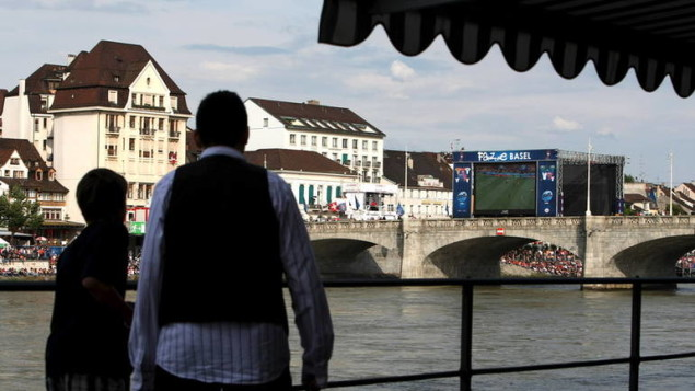 Two spectators look across the river towards the fanzone on the banks of the river Rhine featuring two giant screens 60 sqm / m² on the Mittlere Brücke in Basel during the Spain vs Sweden preliminary round group D match, Switzerland 14 June 2008.  The EURO 2008 soccer tournament held in Switzerland and Austria between  7 and 29 June 2008 is one of the world's major sporting events attracting hundreds of thousands of supporters who travel between the two European countries to watch 16 teams battle it out for the trophy.  EPA/NIC BOTHMA