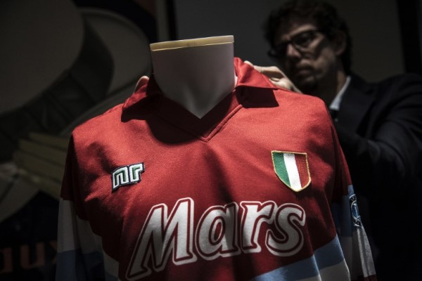 "A man displays a jersey worn by S.S.C. Napoli Argentina's football legend Diego Armando Maradona during the 1990-1991 season from the collection ""Football Memorabilia,"" at the Aste Bolaffi auction house in Turin on December 4, 2018. (Photo by MARCO BERTORELLO / AFP)"