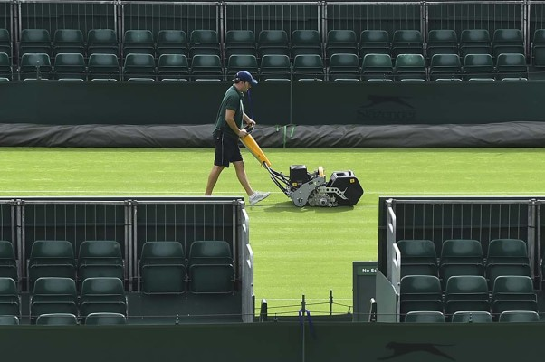 A member of the ground staff mows the grass on a court at The All England Lawn Tennis Club in Wimbledon, southwest London, on July 3, 2017 ahead of play on the first day of the 2017 Wimbledon Championships. / AFP PHOTO / Glyn KIRK / RESTRICTED TO EDITORIAL USE