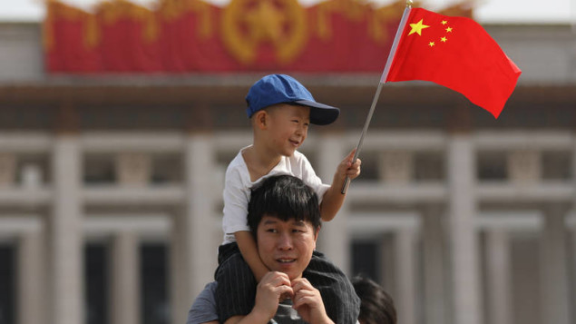epa06237197 A Chinese boy holds a Chinese national flag while sitting on a man's shoulders in Tiananmen Square during National Day celebrations in Beijing, China, 01 October 2017. China celebrates its National Day on 01 October, marking its 68th founding anniversary.  EPA-EFE/WU HONG